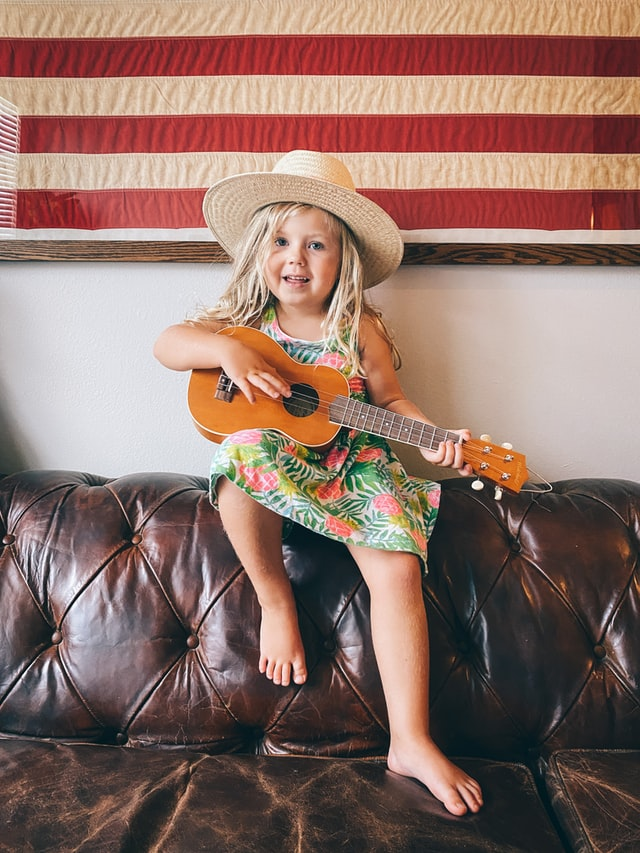 A girl child playing guitar on a summer day in the living room sitting on a couch as a resemblance of child development and music