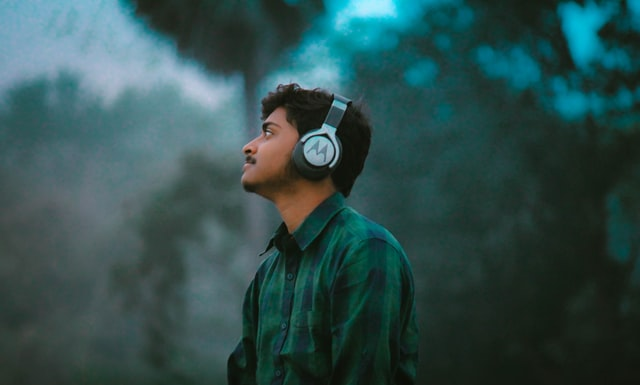 A boy in a checked shirt listening to music on a Motorola headphones in nature.